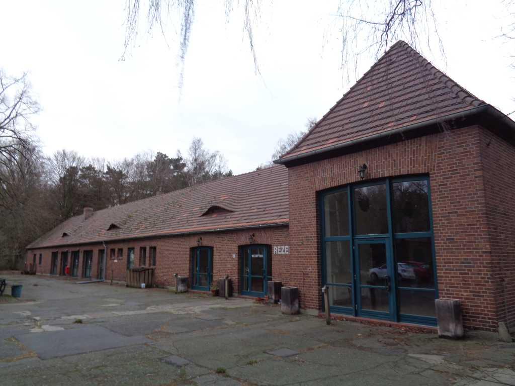 Unsaniertes rotes Backsteingebäude mit grünen Türen der Lotuslicht-Stiftung